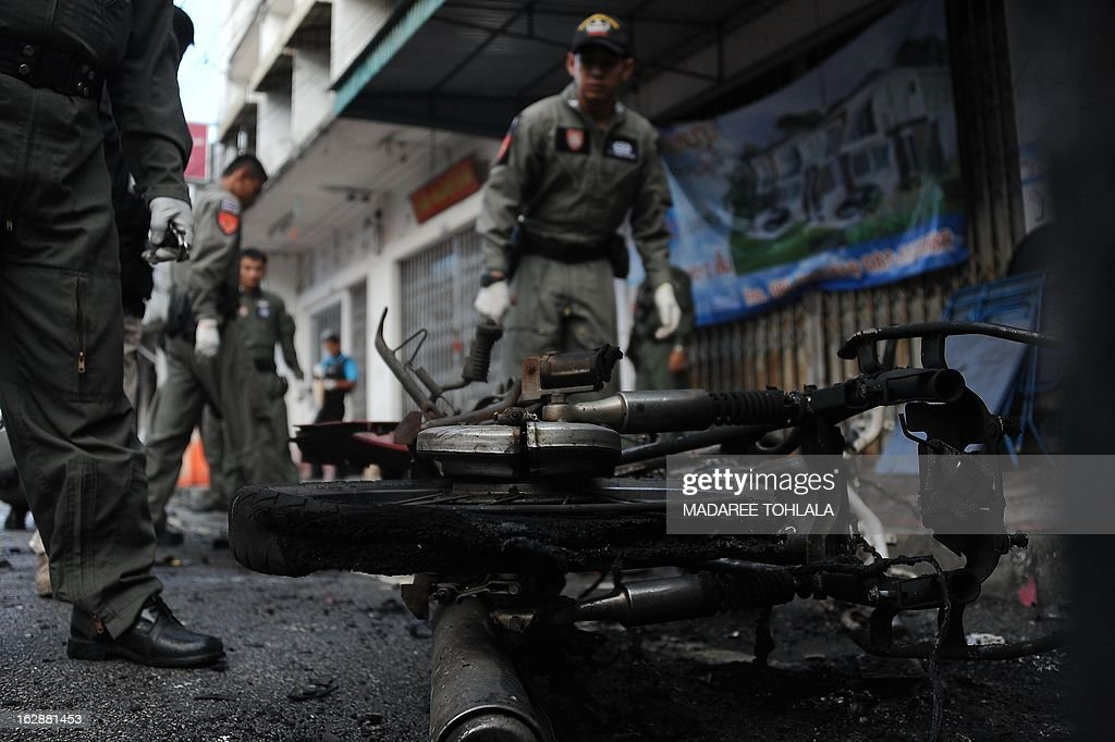 Members of a Thai bomb squad inspect the site of a motorcycle bomb blast triggered by suspected separatist militants in front of a market in Thailand's restive southern province of Narathiwat on March 1, 2013. A bomb blast wounded six people including a soldier early on March 1, police said, a day after Thailand signed its first known agreement with a rebel group in its Muslim-majority south, pledging to work toward talks to end a deadly nine-year insurgency. AFP PHOTO/Madaree TOHLALA