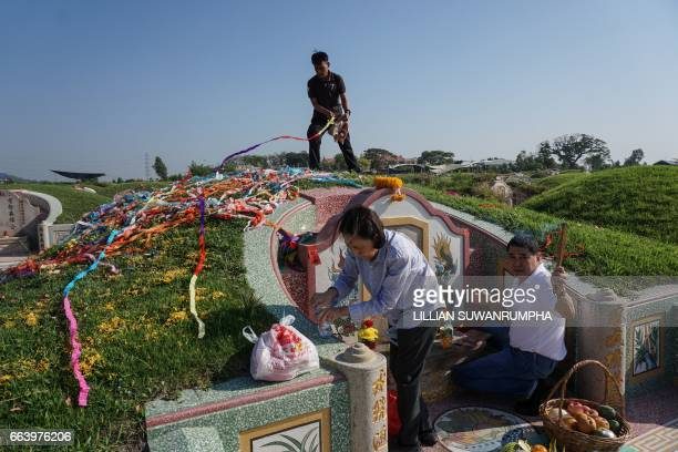 Members of a ThaiChinese family decorate and tidy the tomb of their ancestors ahead of Qingming Festival or Tomb Sweeping Day in a Chinese cemetery...