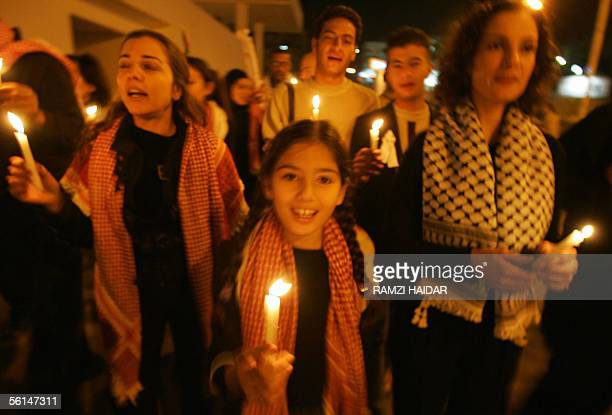 Members of a theater group in Amman hold up candles during an emotional performance 12 November 2005 at the Radisson SAS hotel in which they...