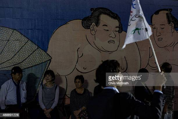 Members of a tour group wait to leave after watching fights during the Tokyo Grand Sumo tournament at the Ryogoku Kokugikan on September 16 2015 in...