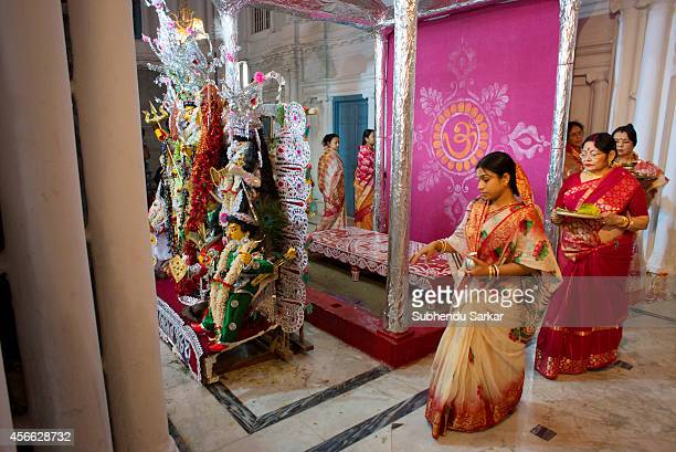 Members of a traditional aristocratic house performing rituals before the idol of Hindu goddess Durga accompanied by her children slaying the demon...