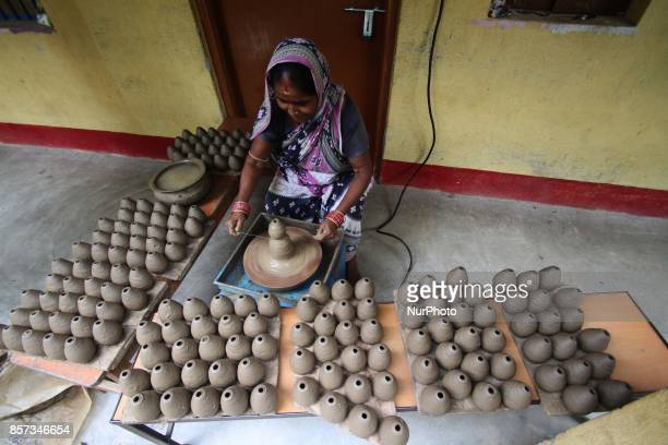 Members of a traditional potter family busy to built fire cracker shells in clay ahead of the festival of lights quotDiwaliquot at a village...