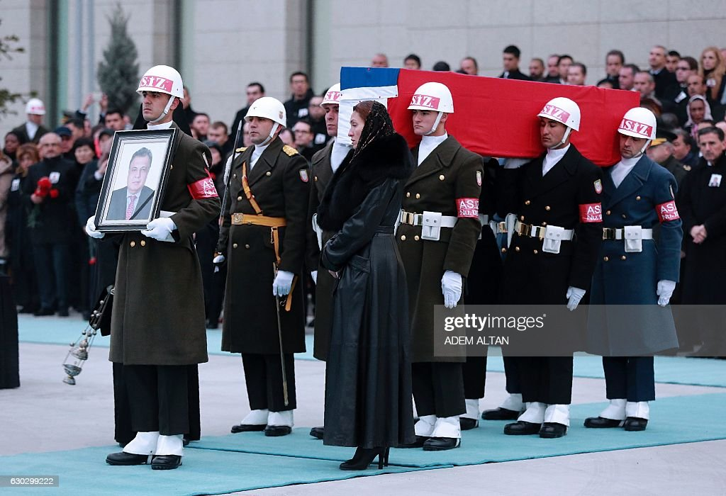 TOPSHOT - Members of a Turkish forces honour guard carry the Russian flag-draped coffin of late Russian Ambassador to Turkey Andrei Karlov and a picture of him during a ceremonial farewell with full state honours on the tarmac of Ankara's Esenboga Airport on December 20, 2016, before the coffin is transported on a Russian plane for Moscow. Veteran diplomat Andrei Karlov was shot nine times in the back by an off-duty Turkish policeman at the opening of an exhibition of Russian photography on December 19, 2016. The brazen killing stunned Ankara and Moscow, which have rowed repeatedly over the Syria conflict but in recent weeks have begun cooperating closely on the evacuations from war-wrecked Aleppo. ALTAN