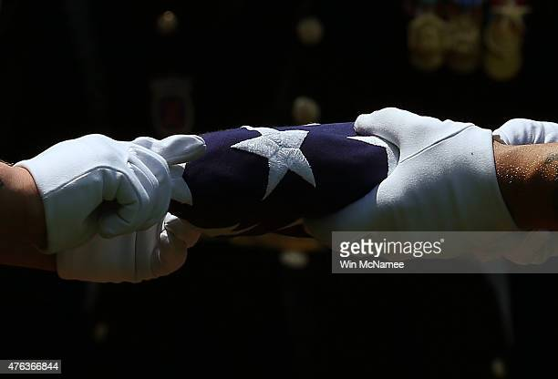Members of a U.S. Army burial team fold the American flag that covered the casket containing the remains of World War II U.S Army Air Forces 2nd Lt....