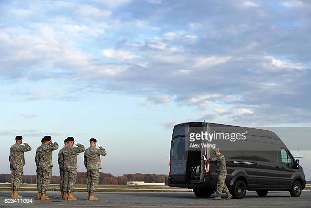 Members of a US Army carry team salute as Air Force Senior Airman Brandon Norton closes the back doors of a transfer vehicle that carries the...
