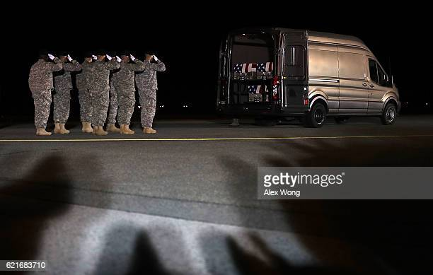 Members of a US Army carry team salute as the flagdraped transfer cases holding the remains of Army Sgt 1st Class Matthew C Lewellen of Lawrence...