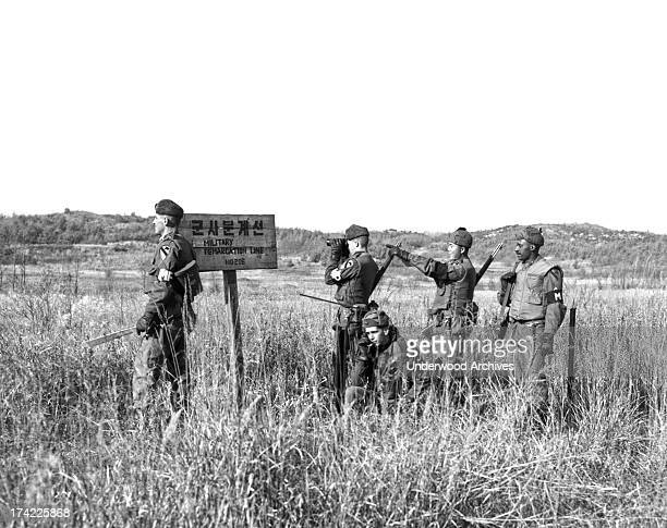 Members of a US Army patrol pause at the Military Demarcation Line for a look into the north South Korea December 6 1962