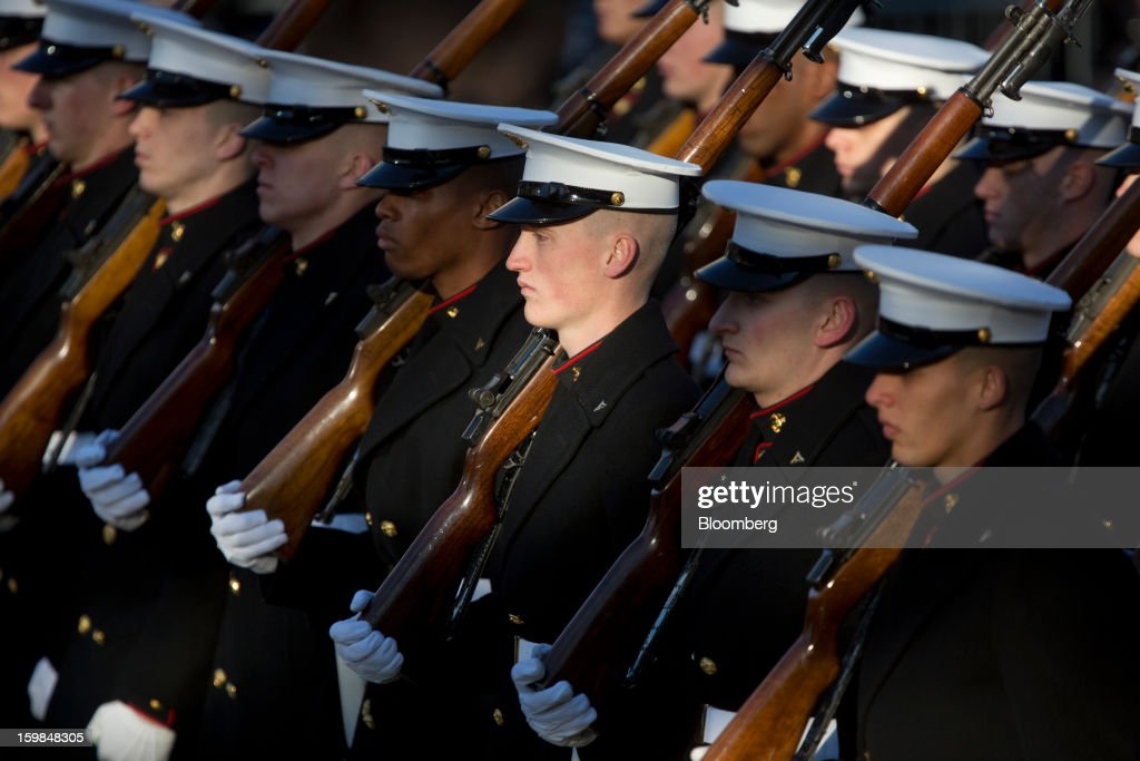 Members of a U.S. Marine Corps Honor Guard hold rifles while standing on the parade route during the presidential inauguration in Washington, D.C., U.S., on Monday, Jan. 21, 2013. A crowd estimated by police to be as large as 700,000, including warmly dressed women with American flags stuck in their hair, a smattering of celebrities and many Republicans, gathered today to witness President Barack Obama take his second oath of office on the steps of the U.S. Capitol. Photographer: Victor J. Blue/Bloomberg via Getty Images