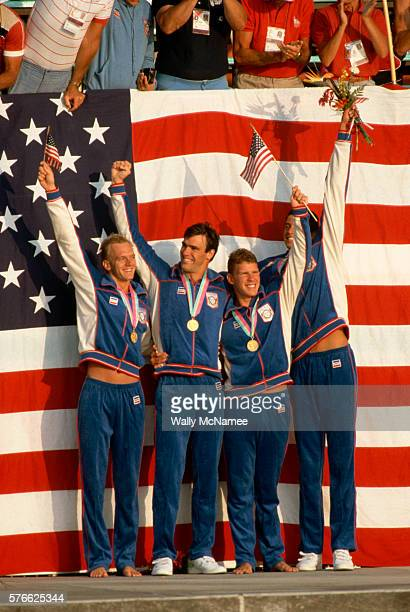 Members of a US men's relay swimming team pose in front of an American flag with their gold medals
