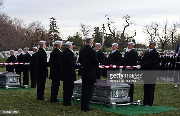 Members of a US Navy ceremonial team remove the Stars and Stripes from the caskets of two unknown sailors who were killed in 1862 when the ironclad...