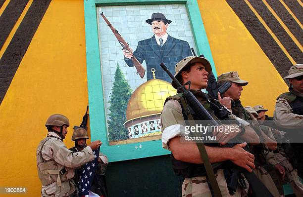 Members of a US Navy combat unit pose April 6 2003 under a Saddam Hussein mural in the Iraqi port town of Umm Qasr Life in Umm Qasr a town that...
