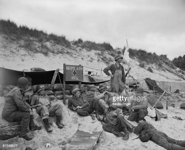 Members of a US Navy First Aid station sit on a sandy beach as they wait for wounded soldiers during the aftermath of the Normandy DDay invasion...