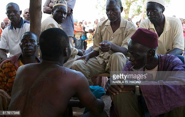 Members of a vigilante group question a man after he was detained upon suspicion of robbery on March 19 2016 in Kokologo Burkina Faso Vigilante...