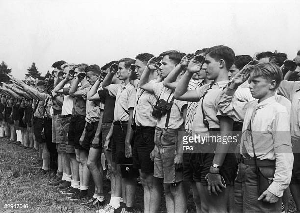 Members of a visiting American youth organization along with members of the Hitler Youth give their respective salutes at a flagraising ceremony near...