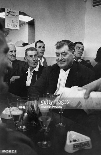 Members of a visiting brass band from Burwash in East Sussex drinking in a cafe bar in Eu SeineMaritime Normandy France September 1955 Original...