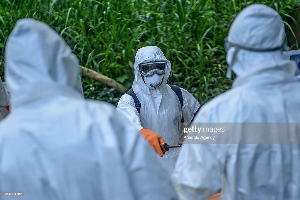 Members of a volunteer medical team wear special uniforms for the burial of 7 people, sterilized after dying due to the Ebola virus, in Kptema graveyard in Kenema, Sierra Leone on August 26, 2014. In recent months, Ebola a contagious disease for which there is no known treatment or cure has claimed at least 1429 lives in West Africa, mostly in Sierra Leone, Guinea and Liberia.