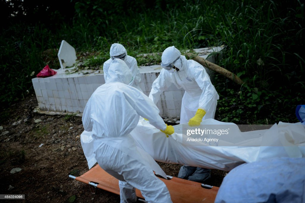 Members of a volunteer medical team wearing special uniforms, carry the body of an Ebola victim during the burial of 7 people died due to the Ebola virus, in Kptema graveyard in Kenema, Sierra Leone on August 26, 2014. In recent months, Ebola a contagious disease for which there is no known treatment or cure has claimed at least 1429 lives in West Africa, mostly in Sierra Leone, Guinea and Liberia.