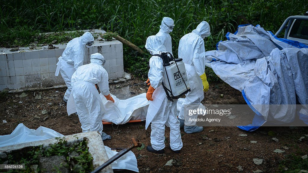 Members of a volunteer medical team wearing special uniforms, sterilize the body of an Ebola victim during the burial of 7 people died due to the Ebola virus, in Kptema graveyard in Kenema, Sierra Leone on August 26, 2014. In recent months, Ebola a contagious disease for which there is no known treatment or cure has claimed at least 1429 lives in West Africa, mostly in Sierra Leone, Guinea and Liberia.