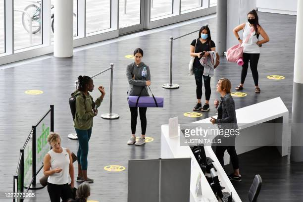 Members of a yoga class wait in a socially distanced queue by the reception area at Kensington Leisure Centre in west London on July 25, 2020 as...