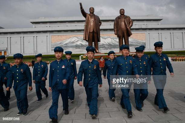 TOPSHOT Members of a 'youth league' leave after paying their respects before the statues of late North Korean leaders Kim Il Sung and Kim Jong Il at...