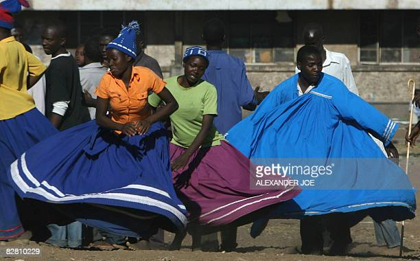 Members of a Zimbabwean religious group sing and dance in Harare on September 14 2008 on the eve of the power sharing deal between Zimbabwean...
