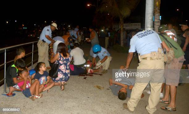 Members of Acapulco tourist police attend injured tourists after a shootout on April 15 2017 in Acapulco Mexico A shootout in the tourist area of the...