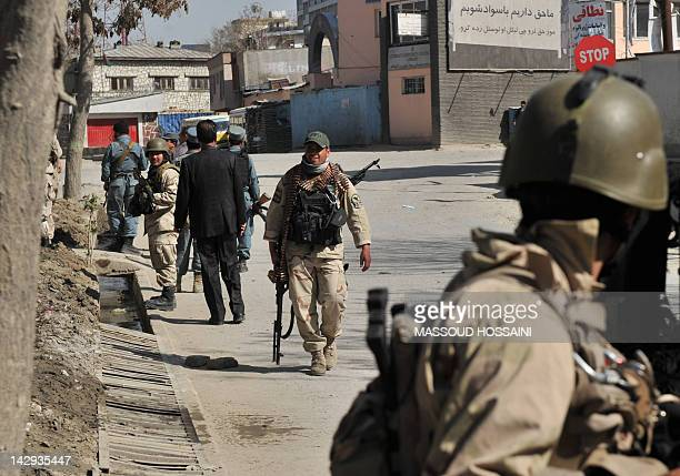 Members of Afghanistan's Ministry of Interior walk near a building being used by insurgents near the scene of an attack in Kabul on April 15 2012 The...