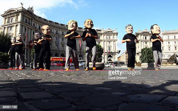 Members of aid agency Oxfam wearing masks of G8 leaders pretend to be pregnant as they take a prenatal yoga class in a demonstration to highlight...