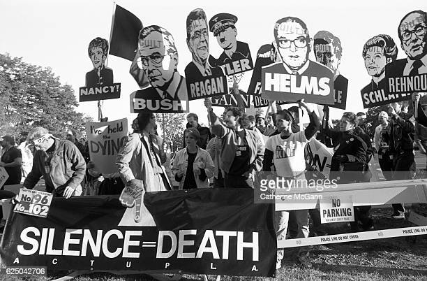 "Members of AIDS activist group ACT UP hold up signs of George W. Bush, Ronald Reagan, Nancy Reagan, Jesse Helms and other with the word ""Guilty""..."
