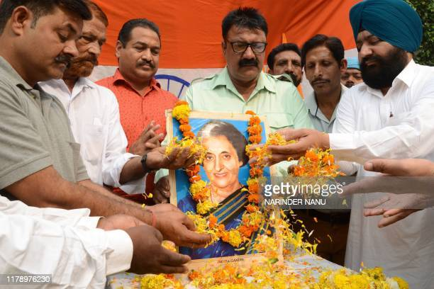 Members of All India Anti Terrorist Front shower flowers petals as they pay tribute to the late former Indian prime minister Indira Gandhi on the eve...