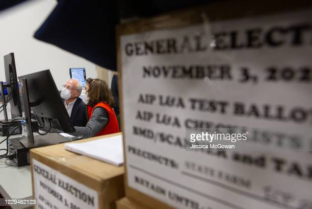 Members of an adjudication review panel look over scanned absentee ballots at the Fulton County Election Preparation Center on November 4, 2020 in...