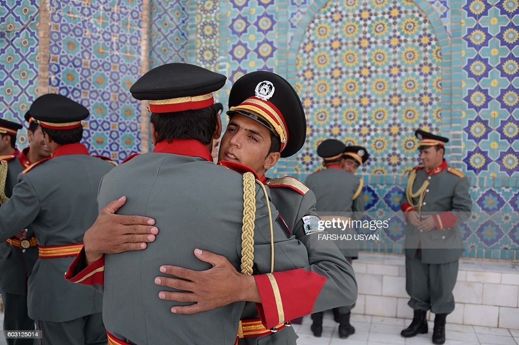 TOPSHOT - Members of an Afghan guard of honour greet each other after offering Eid-al-Adha prayers at the Hazrat-i- Ali shrine in Mazar-i Sharif on September 12, 2016. Afghans started celebrating Eid al-Adha or 'Feast of the Sacrifice', which marks the end of the annual hajj or pilgrimage to Mecca and is celebrated in remembrance of Abraham's readiness to sacrifice his son to God. / AFP / FARSHAD