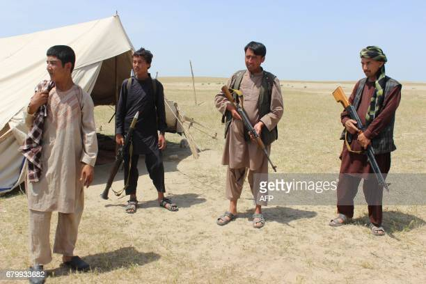 Members of an Afghan militia look on during fighting between Taliban militants and Afghan security forces near the QalaeZal district in Kunduz...