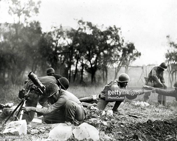 Members of an African American mortar company of the 92nd Division pass the ammunition and heave it over at the Germans in an almost endless stream...