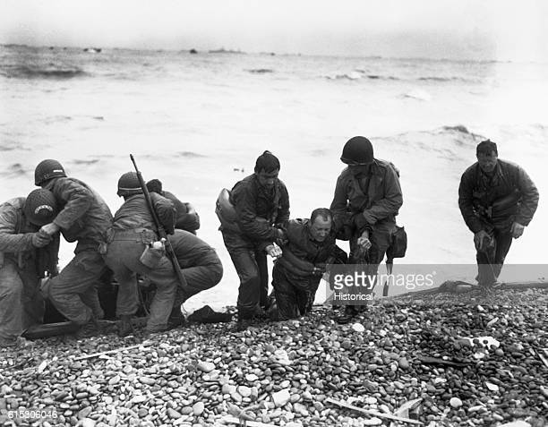 Members of an American landing party lend helping hands to others whose landing craft was sunk by enemy action off the coast of France These...
