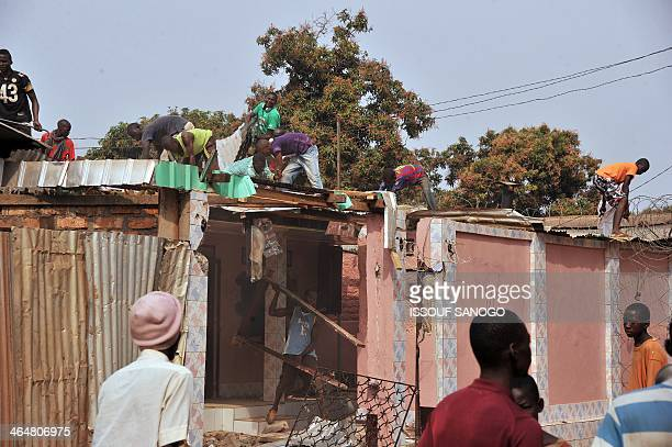 Members of an antiBalaka militia dismantle the roofs of houses belonging to Muslims on January 24 2014 at P12 district in the north of Bangui Central...
