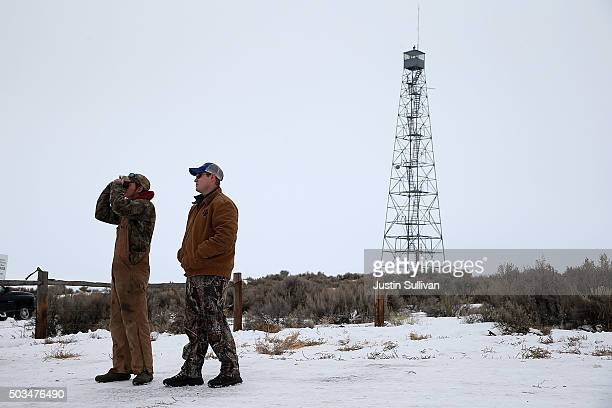 Members of an antigovernment militia stand guard at a checkpoint in front of the Malheur National Wildlife Refuge Headquarters on January 5 2016 near...