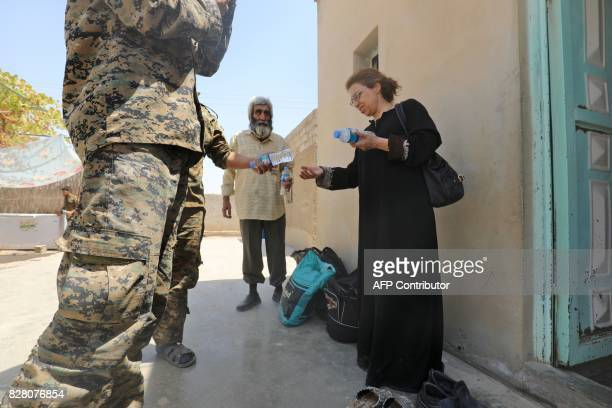 Members of an Armenian Christian family who fled from Raqa receive water from fighters from the Syriac Military Council a Christian unit battling...