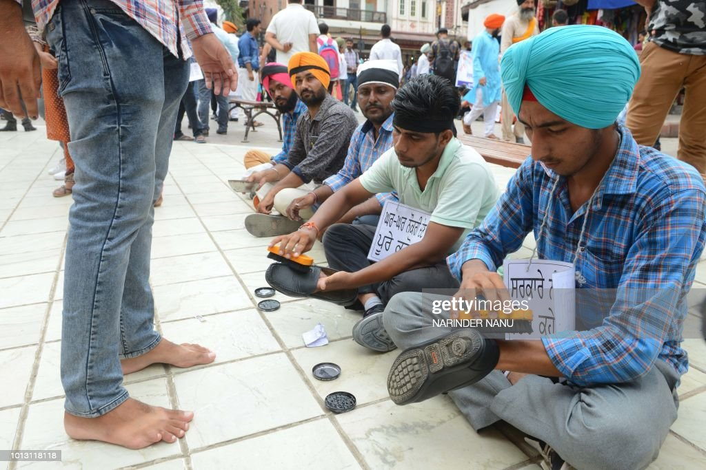 Members of an elementary teachers union polish shoes during a protest against Punjab state government to demand jobs outside Jallianwala Bagh in...