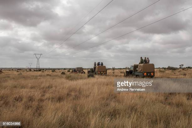 Members of an elephant collaring team wait for elephants to be spotted by the rest of the team in the air before moving to a new location during an...