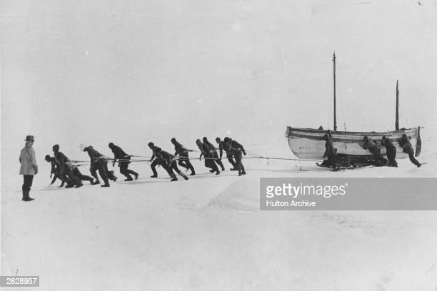 Members of an expedition team led by Irish explorer Sir Ernest Henry Shackleton pull one of their lifeboats across the snow in the Antarctic...