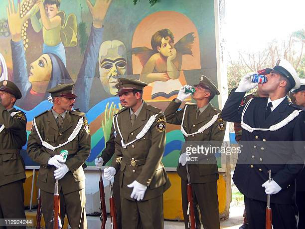 Members of an honor guard quench their thirst in the hot sun as they wait for the Asian Cup champion Iraqi soccer team to arrive at Prime Minister...