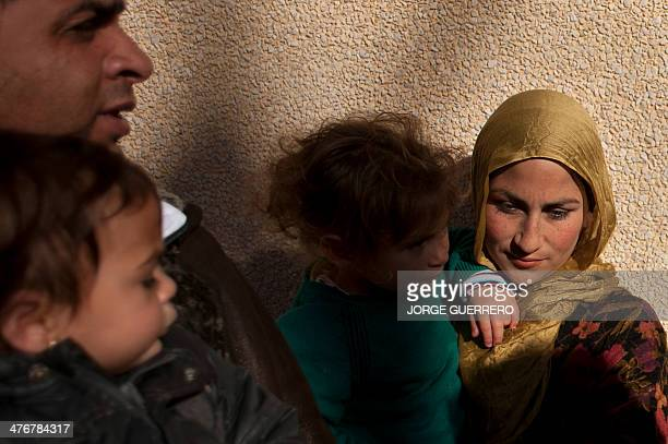 Members of an immigrant family look on at the Centre for Temporary Stay of Immigrants in Ceuta during a visit of Spain's Interior Minister on March 5...