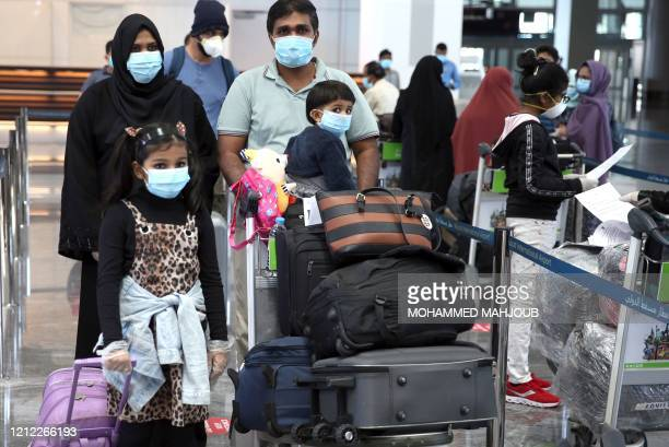 Members of an Indian family check in at the Muscat International Airport before leaving the Omani capital on a flight to return to their country, on...