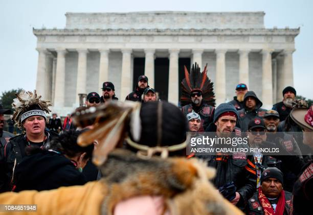 Members of an indigenous bikers group listen to a woman giving them directions to help with security during the Indigenous People's March on the...