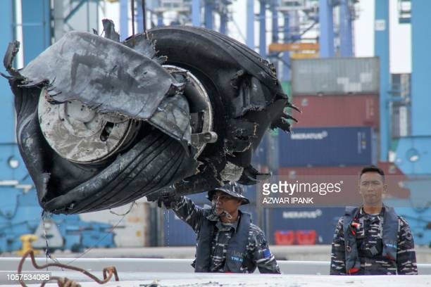 Members of an Indonesian rescue team unload a pair of tyres from the illfated Lion Air flight JT 610 recovered at sea at Jakarta port on November 5...