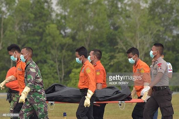 Members of an Indonesian search and rescue team carry a body of a passenger from the AirAsia flight 8501 in Pangkalan Bun on January 5 2015 Weather...