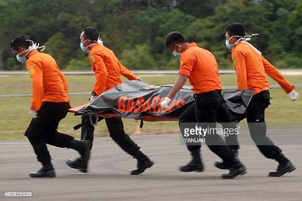 Members of an Indonesian search and rescue team carry a dead body with a stretcher during the recovery of victims who were onboard the crashed...