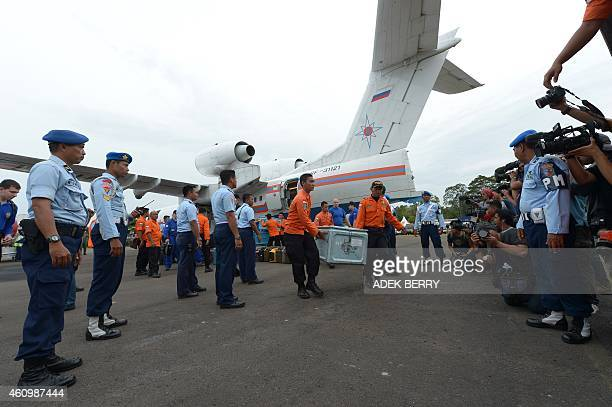 Members of an Indonesian search and rescue team carry equipment after a Russian search and rescue team arrived in a Russian BE200 amphibious aircraft...