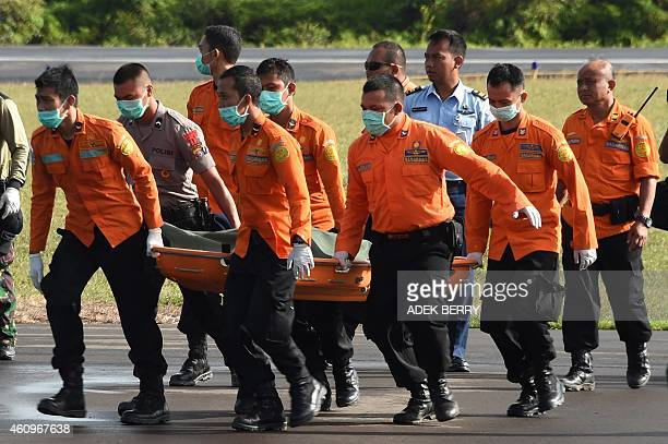 Members of an Indonesian search and rescue team carry the body of a victim recovered in the search for wreckage of AirAsia flight QZ8501 lost over...